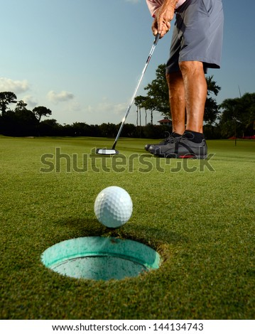 Golfer putting ball in hole on golf course - stock photo