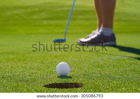 golfer putting ball into hole - stock photo
