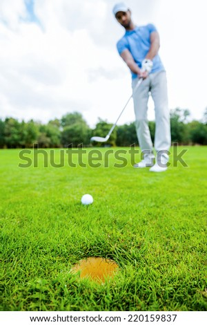 Golfer putting. Full length of young man in sports clothing playing golf while standing on green with hole on foreground - stock photo