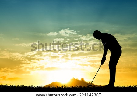 Golfer silhouette at sunset - stock photo