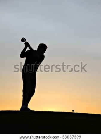Golfer swinging his driver at sunrise. - stock photo