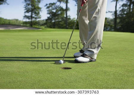 Golfer taps in with putter on a green with trees near a lake - stock photo