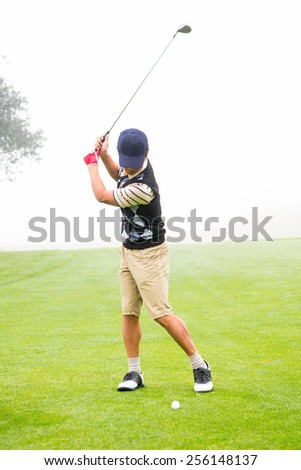 Golfer teeing off at the golf course - stock photo