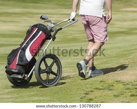 Golfer walking down the fairway on a course with golf bag and trolley - stock photo