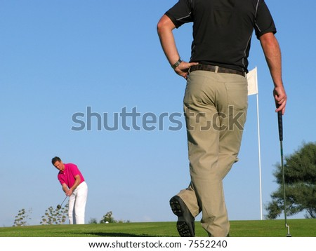 Golfer watching his opponent take a long difficult putt. - stock photo