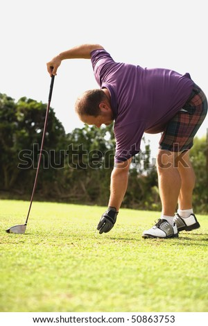 Golfer wearing a purple shirt getting ready to tee off. - stock photo