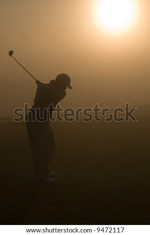 Golfers and a resort golf course in action - stock photo