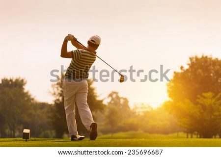 Golfers hit sweeping golf course in the summer - stock photo