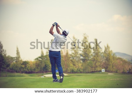 Golfers hit sweeping golf course in the summer vintage color - stock photo