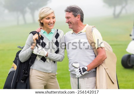 Golfing couple smiling and holding clubs on a foggy day at the golf course - stock photo