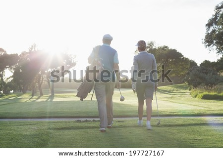Golfing couple walking and chatting on a sunny day at the golf course - stock photo