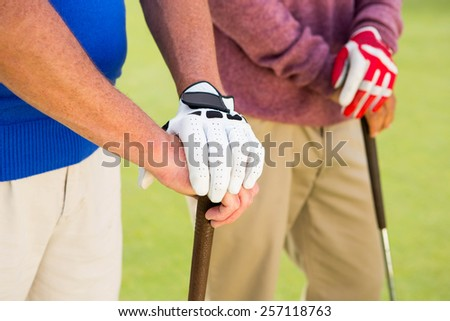 Golfing friends standing and holding clubs at golf course - stock photo