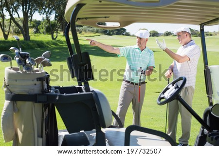 Golfing friends standing beside their buggy looking around on a sunny day at the golf course - stock photo