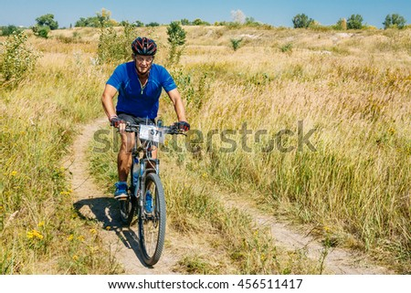 Gomel, Belarus - August 9, 2015: Mountain Bike cyclist riding track in meadow at sunny day, healthy lifestyle active athlete doing sport. - stock photo