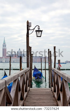 Gondola at the end of the bridge with blue cover in Venice at the pier - stock photo
