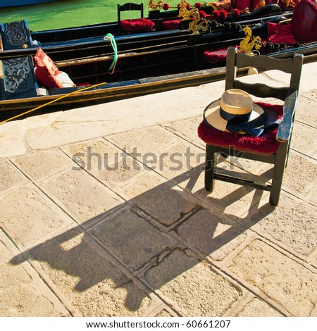Gondola driver waiting chair under the sun proyecting shadow at Venice, Italy - stock photo