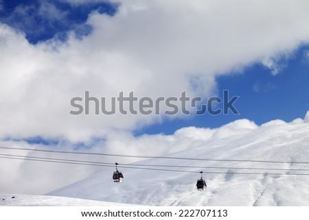 Gondola lifts and off-piste slope at sun day. Caucasus Mountains, Georgia. Ski resort Gudauri. - stock photo