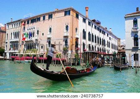 Gondola on Grand Canal in Venice, Italy. Focus on a gondola with a gondolier - stock photo
