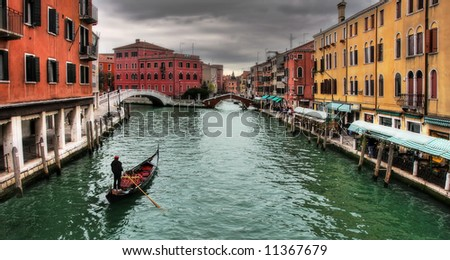 Gondola passing by venetian canal among multicolored houses in Venice. - stock photo