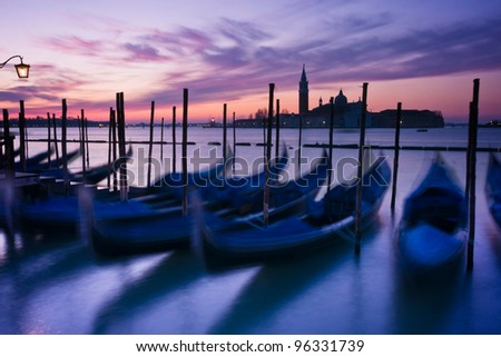 Gondolas moored by Saint Mark's square at dawn with San Giorgio di Maggiore church beyond - Venice, Venezia, Italy, Europe - stock photo