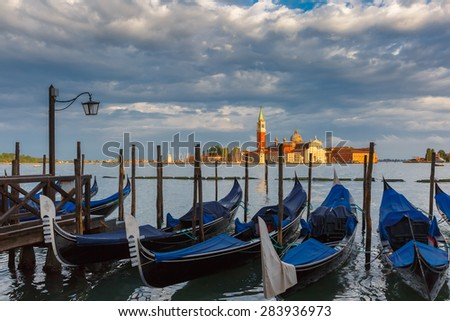Gondolas moored by Saint Mark square with San Giorgio di Maggiore church in the background in Venice lagoon after the storm, Italia - stock photo