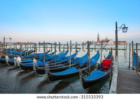 Gondolas moored by Saint Mark square with San Giorgio di Maggiore church in the background - Venice, Venezia, Italy. - stock photo