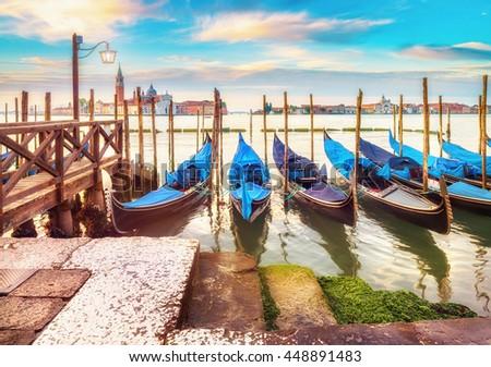 Gondolas moored by Saint Mark square with San Giorgio di Maggiore church in the background. Venice, Venezia, Italy, Europe. This image is toned. - stock photo