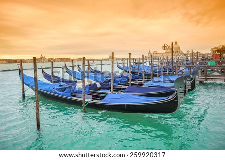 Gondolas moored in the water canal on Riva degli Schiavoni with a view of Santa Maria della Salute church at sunset in Venice, Italy. - stock photo