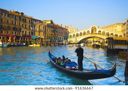 gondolas on the Grand Canal in Venice. Rialto Bridge on background. Sunset - stock photo