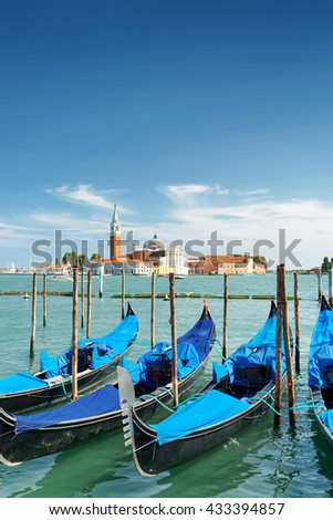 Gondolas parked beside the Riva degli Schiavoni on the Venetian Lagoon in Venice, Italy. The Church of San Giorgio Maggiore on island of the same name is visible in background. - stock photo