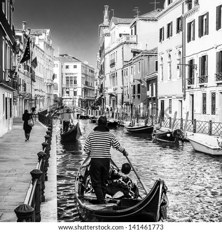 Gondolas passing on small canal among old historic houses and bridge in Venice, Italy. Black and white image. - stock photo