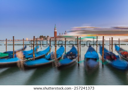 Gondolas rocking on the waves in Venice  - stock photo
