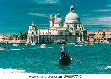 Gondolier in a gondola rides on Canal Grande in a hat with a red ribbon and a typical striped singlet, Basilica di Santa Maria della Salute in the background, Venice, Italy. Selective focus on - stock photo