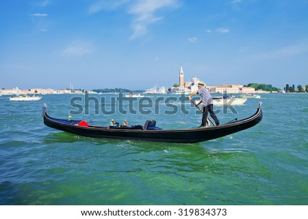 Gondolier on a gondola on the Grand Canal in Venice, Italy. Gondola's are a major mode of touristic transport in Venice - stock photo
