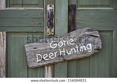 Gone deer hunting sign on old green door. - stock photo