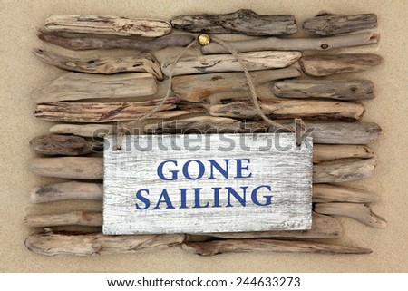 Gone sailing old weathered sign on driftwood and beach sand background. - stock photo