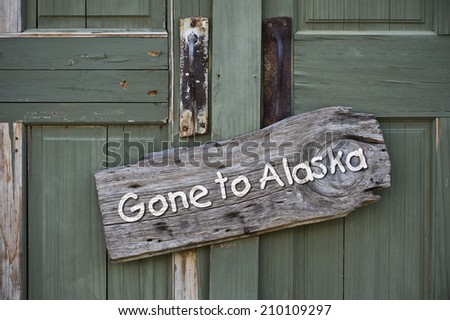 Gone to Alaska sign on old doorway. - stock photo