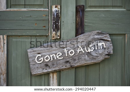 Gone to Austin,Texas sign on old green doors. - stock photo