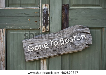 Gone to Boston sign on old green doors. - stock photo