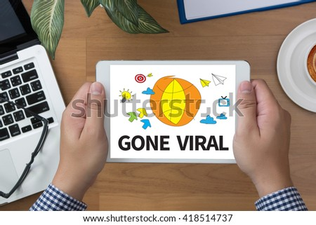 GONE VIRAL man hand Tablet and coffee cup - stock photo
