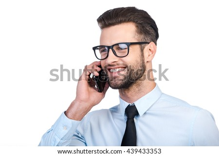 Good business talk. Confident young handsome man in shirt and tie talking on mobile phone and smiling while standing against white background  - stock photo
