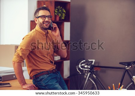 Good business talk. Confident young man talking on the mobile phone and smiling while leaning at the desk in office - stock photo