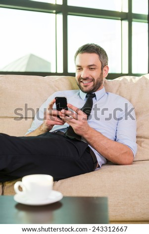 Good business talk. Handsome mature man in shirt and tie talking on the mobile phone and smiling while sitting at his working place - stock photo