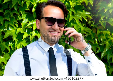 Good business talk. Handsome young man talking on the mobile phone and smiling while standing against decorative trees background.Handsome Young urban businessman using smartphone  - stock photo
