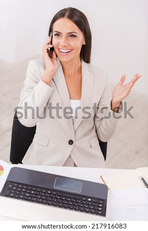 Good business talk. Top view of beautiful young businesswoman talking on the mobile phone and smiling while sitting at her working place - stock photo
