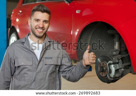 Good Car Brakes. Smiling car mechanic posing against red car on a lift and showing thumb up. Waist up shot in auto repair shop. - stock photo