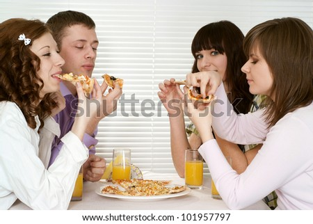Good Caucasian charming company of four people sit and eat pizza at a cafe - stock photo