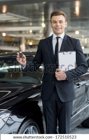 Good choice! Handsome young classic car salesman standing at the dealership and holding a key - stock photo