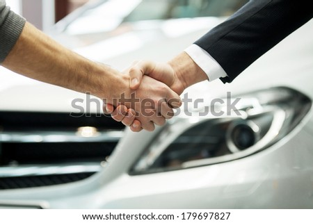 Good deal. Close-up shot of the hands shaking in front of the car - stock photo
