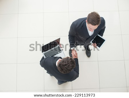 Good deal. Two young successful businessmen are standing with tablet and laptop and shaking their hands. View from the top - stock photo
